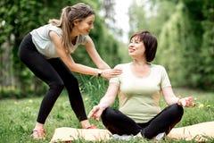 Молодая и старшая женщина делая йогу в парке Стоковые Изображения