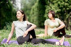 Молодая и старшая женщина делая йогу в парке Стоковое Изображение RF