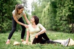 Молодая и старшая женщина делая йогу в парке Стоковое фото RF