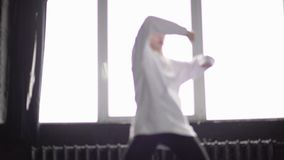 Молодая и стильная девушка в белизне одевает хмель танца тазобедренный в замедленном движении сток-видео