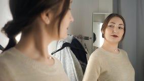 Молодая и счастливая женщина брюнета в магазине одежд усмехаясь и выбирая новые вещи сток-видео
