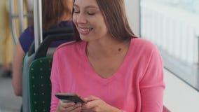 Молодая и счастливая женщина используя смартфон пока сидящ около окна в общественном транспорте во время отключения видеоматериал