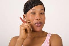 Молодая и усмехаясь женщина держа губную помаду стоковая фотография