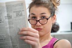 Молодая и усмехаясь женщина при стекла, читая газету Стоковые Фото