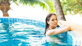 Молодая и sporty женщина в купальнике Девушка ослабляя в бассейне на лете Стоковые Фото