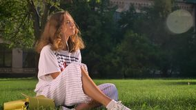 Молодая кавказская девушка брюнет сидит в парке на траве и слушает к музыке на наушниках на smartphone сток-видео