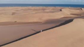 Молодая кавказская девушка в бегах одежд лета вдоль края дюны в пустыне на заходе солнца maspalomas gran canaria сток-видео