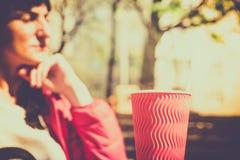 Молодая кавказская девушка сидит в кафе офиса с кофе на таблице в кафе Стоковая Фотография
