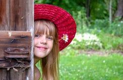 Молодая кавказская девушка peeking вокруг двери стоковое изображение rf
