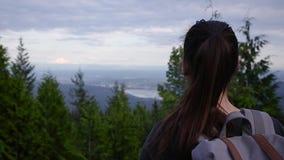 Молодая кавказская женщина брюнета приходя в рамку с взглядом Ванкувера от пункта бдительности на moutnain видеоматериал