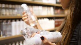 Молодая кавказская женщина покупая этичные продукты сливк заботы тела в супермаркете 4K видеоматериал