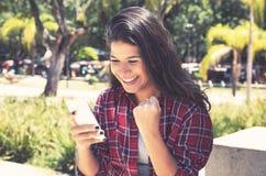 Молодая кавказская женщина получая хорошие новости на телефоне стоковое фото