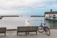 Молодая кавказская женщина сидит с ее задней частью на деревянной скамье обозревая Балтийское море на набережной в Копенгагене Да стоковые изображения rf