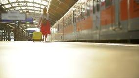 Молодая кавказская женщина с чемоданом бежать для того чтобы уловить поезд внутри прежде чем он выйдет станция без ее акции видеоматериалы