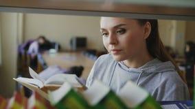 Молодая кавказская красивая студентка стоящая близко полка с книгами в большом просторном удерживании библиотеки одном, поворачив акции видеоматериалы