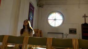 Молодая кавказская религиозная посвященная женщина на стенде в католической церкви сток-видео
