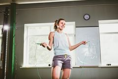 Молодая кавказская усмехаясь женщина держа прыгая веревочку - концепция здоровья и фитнеса стоковые фото