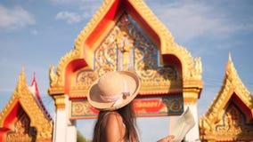 Молодая карта чтения женщины смешанной гонки туристская и исследуя тайский буддийский висок phuket Таиланд 4K, Slowmotion сток-видео