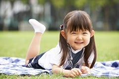 Молодая китайская девушка лежа на одеяле в парке Стоковые Фото