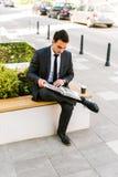 Молодая книга чтения бизнесмена пока кофе пить внешний Стоковые Фотографии RF