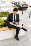 Молодая книга чтения бизнесмена пока кофе пить внешний Стоковая Фотография