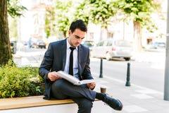 Молодая книга чтения бизнесмена пока кофе пить внешний Стоковые Фото