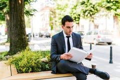 Молодая книга чтения бизнесмена пока кофе пить внешний Стоковая Фотография RF