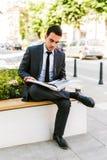 Молодая книга чтения бизнесмена пока кофе пить внешний Стоковые Изображения RF