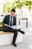 Молодая книга чтения бизнесмена пока кофе пить внешний Стоковое Изображение RF