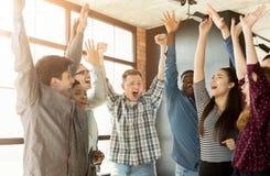 Молодая команда дела наслаждаясь успехом на офисе стоковые фото