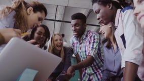 Молодая команда работая на новом проекте Группа в составе люди смешанной гонки стоя около таблицы и обсуждая видеоматериал