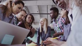 Молодая команда работая на новом проекте Группа в составе люди смешанной гонки стоя около таблицы и обсуждая акции видеоматериалы