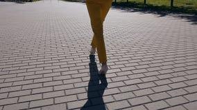 Молодая коммерсантка в костюме и ботинках с пятками идет к городу Конец-вверх женских тонких ног идя через акции видеоматериалы