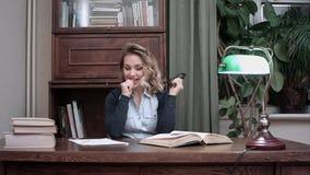 Молодая коммерсантка в стеклах думая над ее проектом и внезапно имея идею гения Стоковые Фотографии RF
