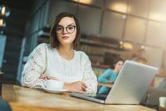 Молодая коммерсантка в стеклах сидит в кафе на таблице перед компьтер-книжкой Студент изучать онлайн Стоковая Фотография RF