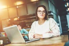 Молодая коммерсантка в стеклах сидит в кафе на таблице перед компьтер-книжкой Студент изучать онлайн Стоковые Фото
