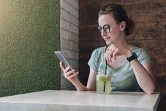 Молодая коммерсантка в стеклах сидя в кафе на таблице, выпивая напитке и используя smartphone Использование девушки битника Стоковое Фото