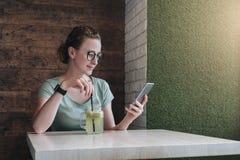 Молодая коммерсантка в стеклах сидя в кафе на таблице, выпивая напитке и используя цифровое устройство Использование девушки битн Стоковое Изображение RF