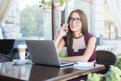 Молодая коммерсантка говоря на телефоне в кафе Стоковое Фото