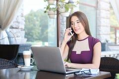 Молодая коммерсантка говоря на телефоне в кафе Стоковые Изображения RF