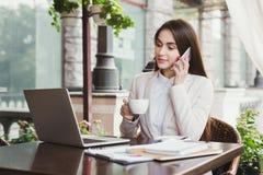 Молодая коммерсантка говоря на телефоне и выпивая кофе outdoors Стоковые Изображения RF