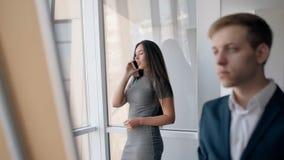 Молодая коммерсантка говоря на телефоне, сочинительстве бизнесмена в современных размерах офиса сток-видео