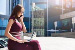 Молодая коммерсантка говоря на телефоне outdoors Стоковые Фото