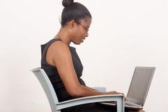 Молодая коммерсантка работая на компьтер-книжке на серой предпосылке стоковое фото
