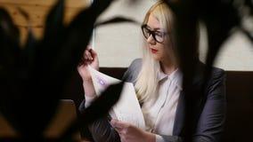 Молодая коммерсантка работая с компьтер-книжкой и документами в кафе сток-видео