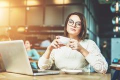 Молодая коммерсантка сидя в кафе на таблице, выпивая кофе и работая на компьтер-книжке Студент изучать онлайн Стоковая Фотография