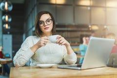 Молодая коммерсантка сидя в кафе на таблице, выпивая чае и работая на компьтер-книжке Студент изучать онлайн Стоковое Изображение RF