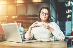 Молодая коммерсантка сидя в кафе на таблице, выпивая чае и работая на компьтер-книжке Студент изучать онлайн Стоковые Изображения RF