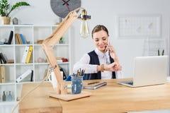 Молодая коммерсантка сидя в офисе на ее столе смотря наручные часы и говорить стоковое изображение rf