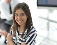 Молодая коммерсантка сидя на столе в офисе стоковые фотографии rf